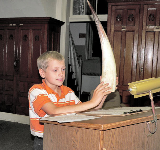 Young Joel Senecal-Moseley shows the Hoosick Town Board a cattle horn he brought back from his recent missionary trip to Uganda. (Bea Peterson photo)