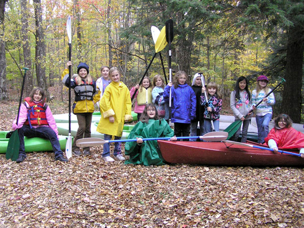 Girls from girl scout troop 1752 pose with kayaks at the dyken pond
