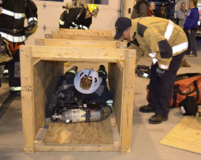Hoosick Falls Assistant Chief Paul Davendonis, guided by NYS Office of Fire Prevention instructor Daniel MacIntyre, works his way through a simulated tight spot, pushing his air tank in front of him. (Bea Peterson photo)