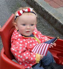 Little Allison June Bushey, dressed all in red, white and blue, waits in fascination for the next group to pass in the Hoosick Falls Memorial Day Parade on Monday. (Bea Peterson photo)