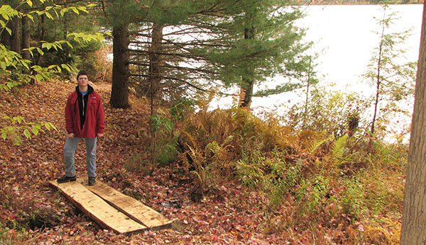 Michael Zlotnick stands by one of the bridges on the walking path he created along the north side of the lake at the Cherryplain State Park for his Eagle Scout project. Photo courtesy of Andrew Zlotnick